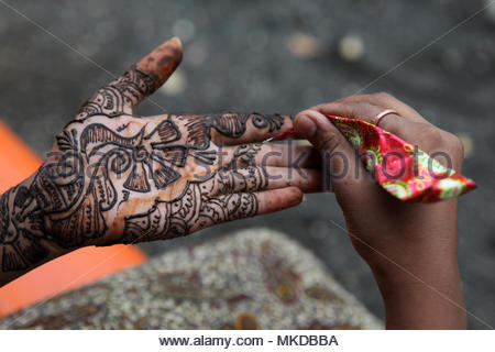 Nagpur, Maharashtra, India - A Maharastrian girl applies a pretty henna design on her hand. - Stock Photo