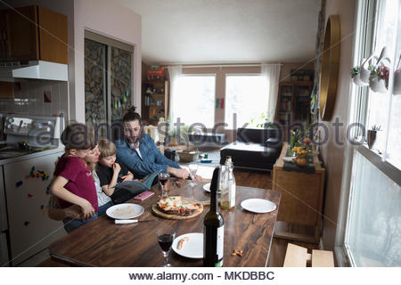 Family eating homemade pizza and reading book at dining table - Stock Photo