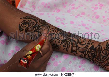 Nagpur, Maharashtra, India - A Maharastrian girl applies a pretty henna design on her hand and arm. - Stock Photo