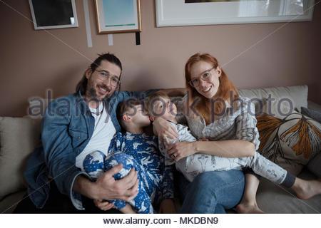 Portrait smiling, happy family on living room sofa - Stock Photo