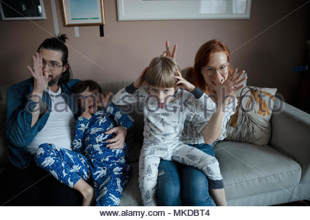 Portrait playful family making faces, gesturing on living room sofa - Stock Photo