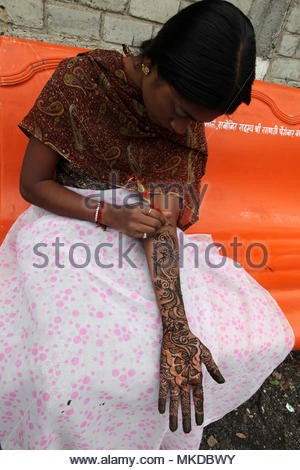 Nagpur, Maharashtra, India - A Maharastrian girl applies a pretty henna design on her hand and arm while sitting on a bench outside a small Hindu temp - Stock Photo