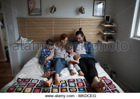 Family reading bedtime story book on bed - Stock Photo