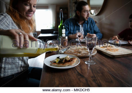 Woman pouring olive oil over homemade pizza at dining table - Stock Photo