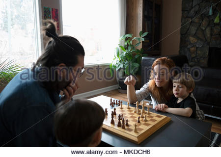 Family playing chess on living room coffee table - Stock Photo