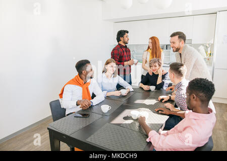 closeup side view shot united group of young people spending time in the kitchen - Stock Photo