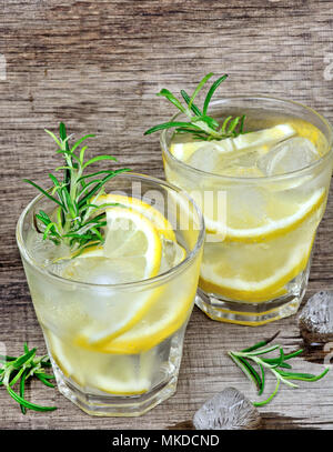 Detox water with sliced lemon and rosemary in a glasses on wooden table - Stock Photo