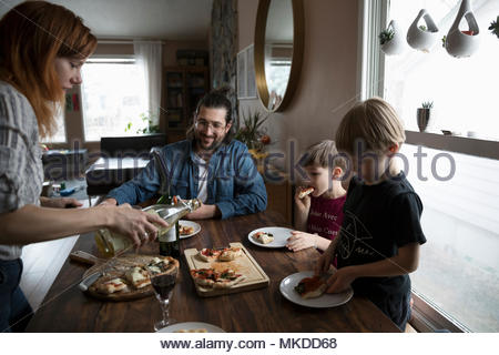 Family eating homemade pizza at dining table - Stock Photo