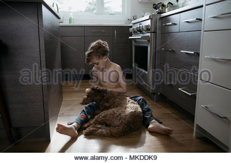Affectionate bare chested boy cuddling, petting dog on kitchen floor - Stock Photo