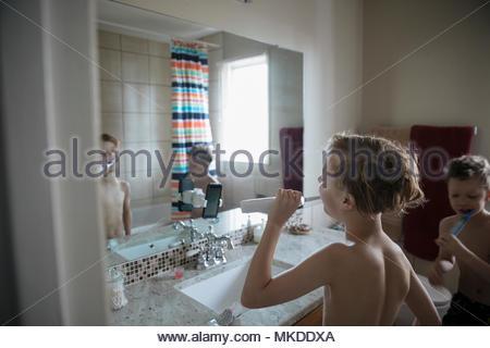 Bare chested boy brushing teeth in bathroom mirror - Stock Photo