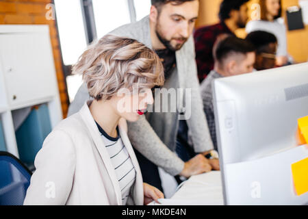 Startup good-looking business partners working together in loft office.close up photo of beautiful stylish secretary working with computer with blurre - Stock Photo