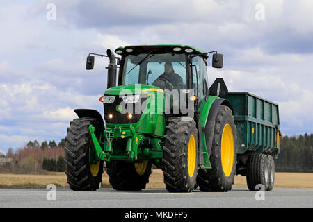Farmer drives John Deere 6150R tractor and agricultural trailer on road. In 2018, late spring delays seeding. Jokioinen, Finland - April 30, 2018. - Stock Photo