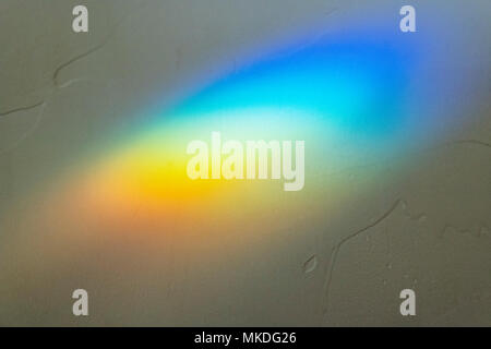 Sunlight through stained glass creates abstract prism effect on wall - Stock Photo