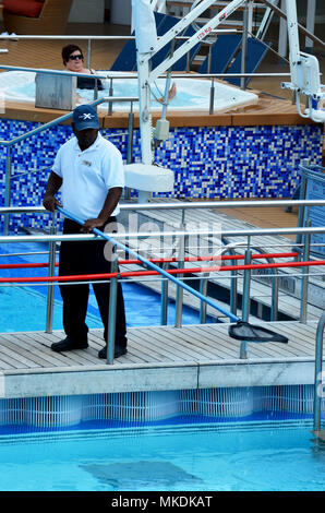 Man cleaning pool on cruise ship - Stock Photo