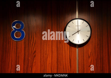 Number 88. Clock on wall showing eight o'clock next to number eight sign lucky eighty eight. - Stock Photo