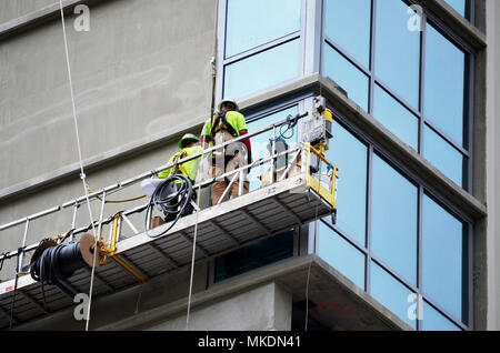 Construction workers on hoist - Stock Photo