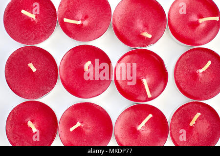 Scented tea light candles on a white background. Close up collection of red candles in metal base. - Stock Photo