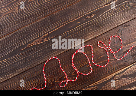 Text love written with thread. Word love on vintage wooden background, copy spce. - Stock Photo
