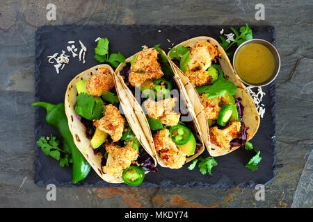 Roasted coconut cauliflower tacos. Healthy, vegan meal. Above view on a dark slate stone background. - Stock Photo