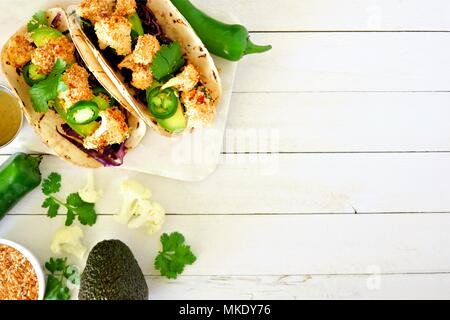 Roasted coconut cauliflower tacos. Healthy, vegan meal. Top view, side border with copy space on a white wood background. - Stock Photo