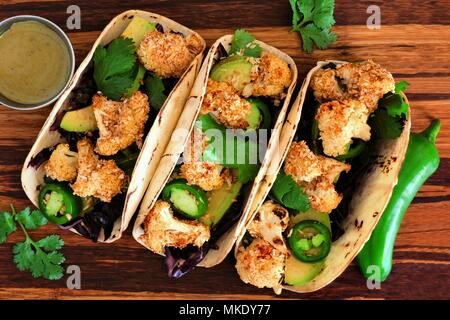 Roasted coconut cauliflower tacos. Healthy, vegan meal. Top view on a wooden background. - Stock Photo