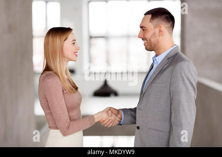 smiling businesswoman and businessman at office - Stock Photo