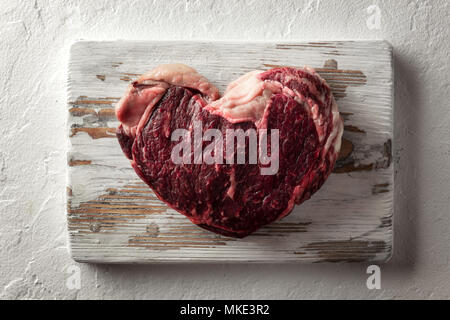 Marbling ribeye steak on wooden plate - Stock Photo