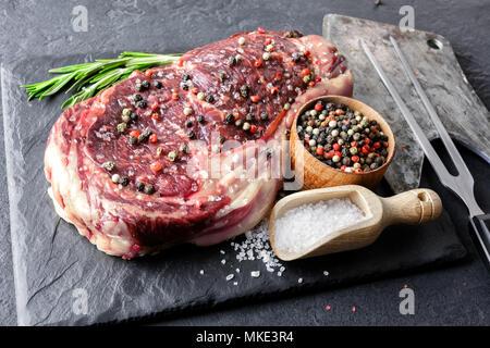 Marbling ribeye steak on black plate - Stock Photo