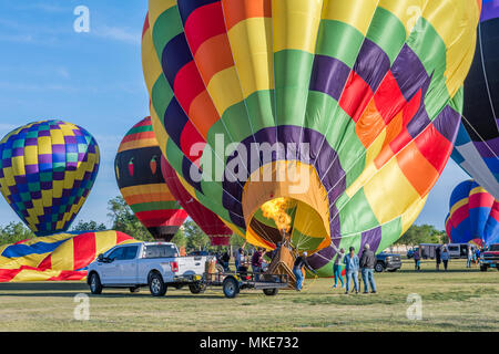 Colorful hot air balloon inflating with burner directing a flame into the envelope at a festival in New Mexico, USA. - Stock Photo