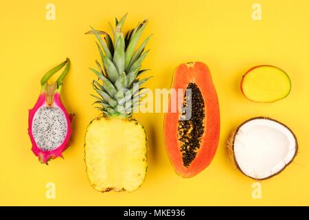 Tropical fruit flat lay with cut pineapple, dragon fruit, papaya, mango, and coconut on a white background - Stock Photo