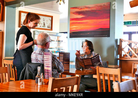 Young waitress taking a food order from a middle aged couple at a table in the Knott End Cafe at Knott End,Wyre,Lancashire,UK - Stock Photo