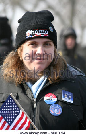 A young woman holding an American flag and covered with button supporting President Obama during his inaugural ceremonies on The National Mall in Wash - Stock Photo