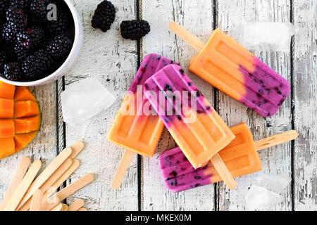 Group of homemade mango blackberry popsicles, top view on a rustic white wood background - Stock Photo