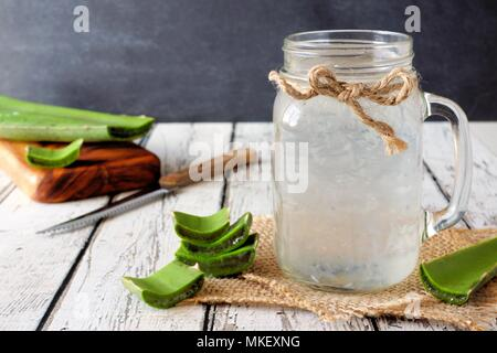 Healthy Aloe vera juice in a mason jar glass. Still life, side view on white wood. - Stock Photo