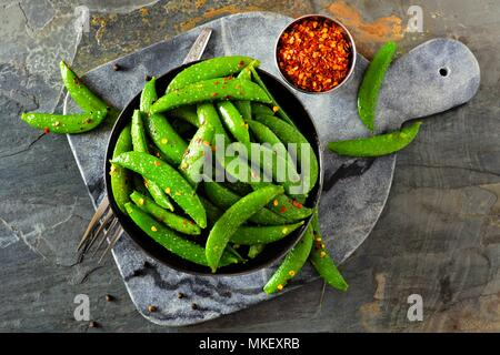 Bowl of healthy roasted snap peas. Top view, flat lay on a dark paddle board over a slate background. - Stock Photo