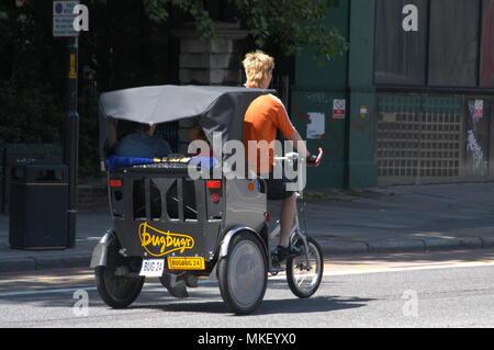 one of the many London three wheel Taxi Bikes - Stock Photo