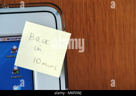 back in 10 minutes Post-it Note sticky note reminder stuck on office computer in a city office - Stock Photo