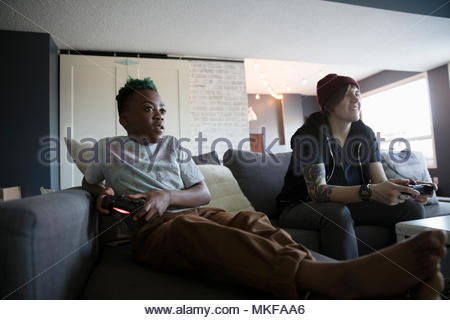Babysitter and boy playing video game on sofa - Stock Photo