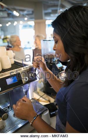 Female barista working at espresso machine in cafe - Stock Photo