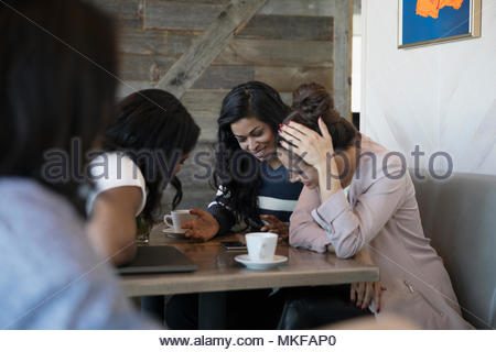 Women friends drinking coffee and using smart phone in cafe - Stock Photo
