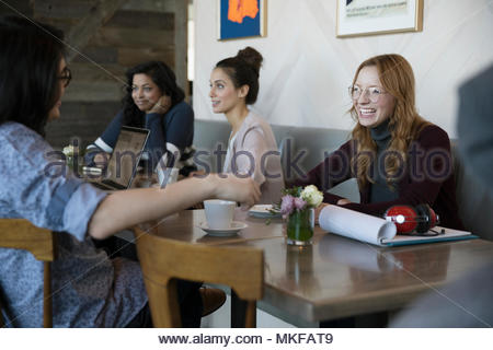 Smiling young couple talking in cafe - Stock Photo