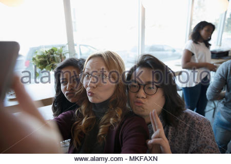 Playful, silly young friends making a face, posing for selfie - Stock Photo