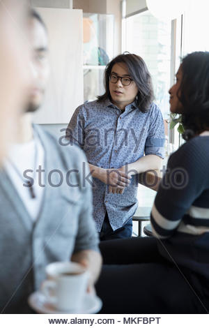 Young man talking with friends in cafe - Stock Photo