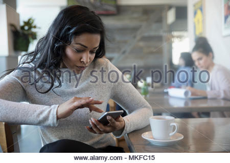 Woman using smart phone, drinking coffee in cafe - Stock Photo