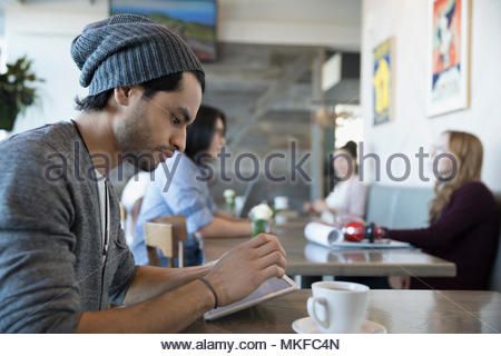 Young man using digital tablet and drinking coffee in cafe - Stock Photo