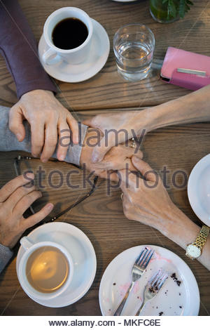 View from above women holding hands, comforting friend in cafe - Stock Photo