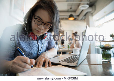 Creative young man writing in notebook, working at laptop in cafe - Stock Photo