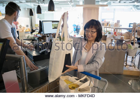 Smiling senior woman placing reusable bags in shopping cart at grocery store checkout - Stock Photo
