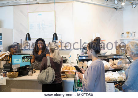 Female worker helping customers in bakery - Stock Photo