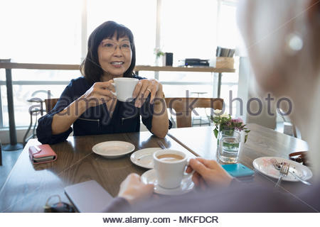 Active senior women friends drinking coffee and talking at cafe - Stock Photo